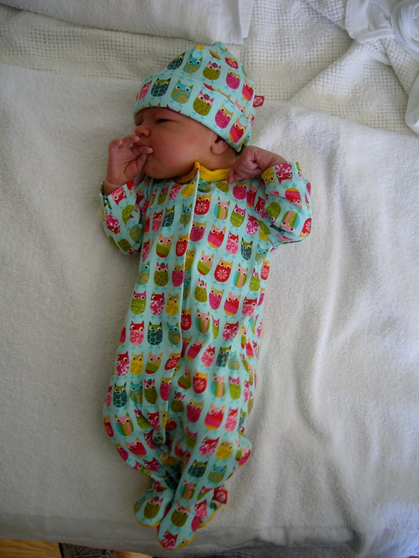 Newborn baby in sleeper and hat