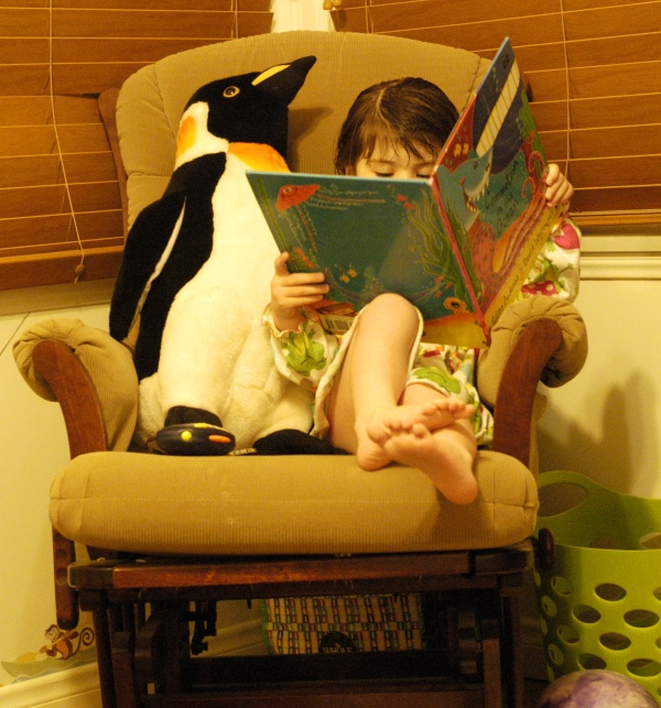 little girl reading in chair
