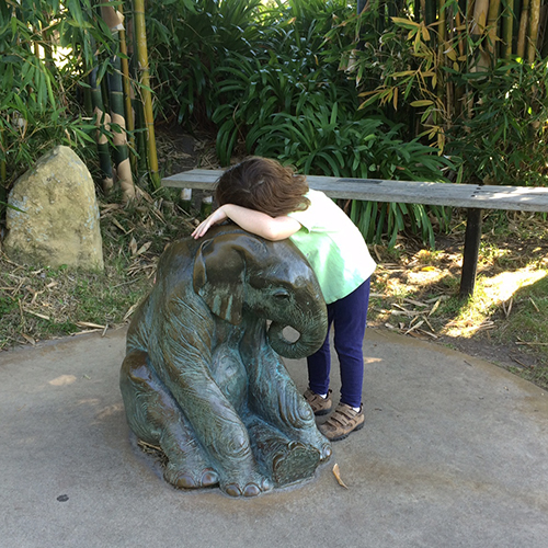 small girl leaning on elephant statue