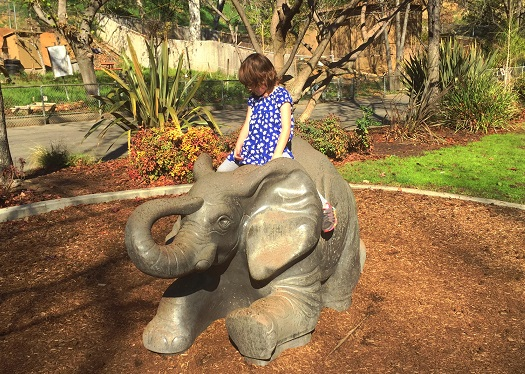 small girl sitting on statue of elephant