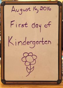 "white board with date and ""first day of kindergarten"" written on it, and a drawing of a flower"