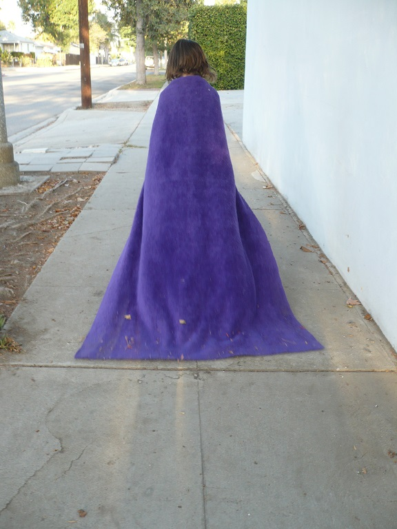 Small girl in purple cloak walking away