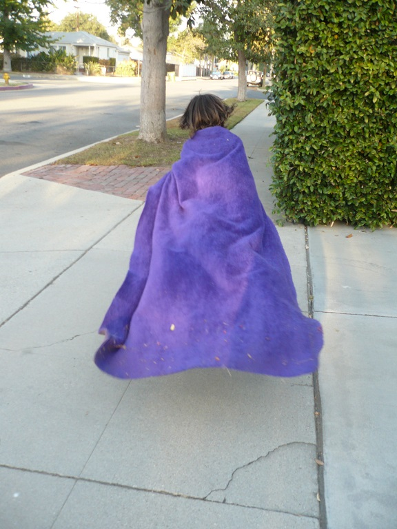 Small girl in purple cloak running