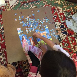 small girl working on 250-piece puzzle with an image of a girl, rabbits, fox, tree, flowers, and deer