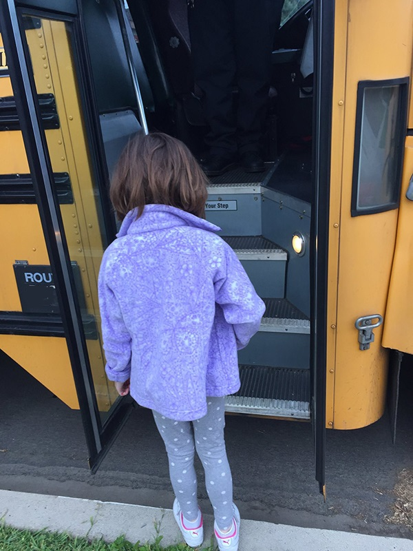 little girl boarding school bus